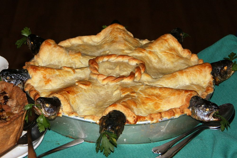 The fish heads pointing out of the pie's top give this pastry its name — Jonathunder / Wikimedia Commons